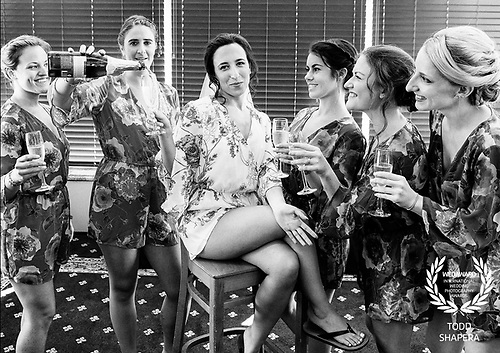 A bride and her bridesmaids uncork champagne in the bridal suite of Tarrytown House Estate before the wedding.