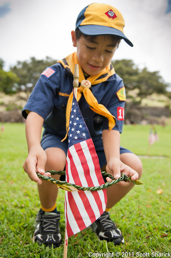 A member of the Boy Scouts adds a lei around an American Flag at Punchbowl Cemetery. Images taken at the National Cemetery of the Pacific in preparation for Memorial Day 2011.