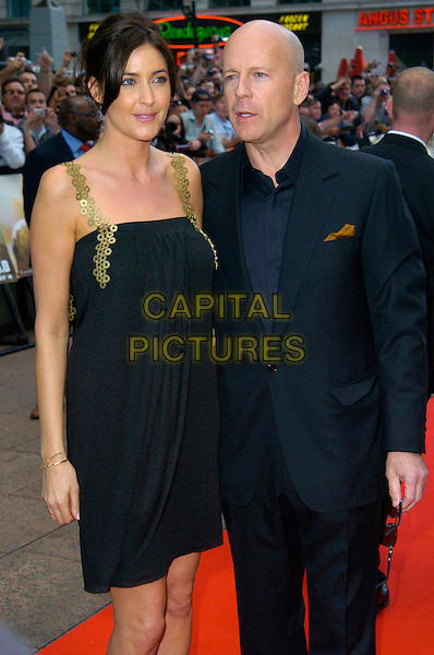 "LISA SNOWDON & BRUCE WILLIS.UK premiere of ""Die Hard 4.0: Live Free or Die Hard"" at the Empire Leicester Square, London, England. .June 20th, 2007.half 3/4 length black dress gold shoes straps circles suit.CAP/CAN.©Can Nguyen/Capital Pictures"