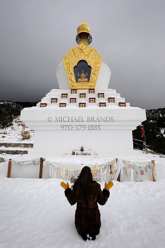 "Elianna Krakauer, of Crestone, meditates at the Tashi Gomang Stupa in Crestone, CO. ""I don't know if this is what the Buddists do (raising hands during meditation), but this is what I do in my personal practice. It's a gesture of opening and surrender."" Michael Brands for The New York Times."