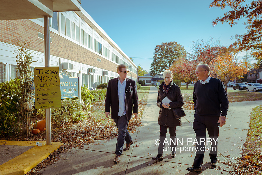 Merrick, New York, USA. Nov. 11, 2016.  At left, DAVID G. MCDONOUGH (Rep - District 14), New York State Assemblyman; his wife CAROLYN MCDONOUGH; and one of their sons; go to vote for President and state and local officials at Polling Place at Park Avenue Elementary School. McDonough is running for re-election.