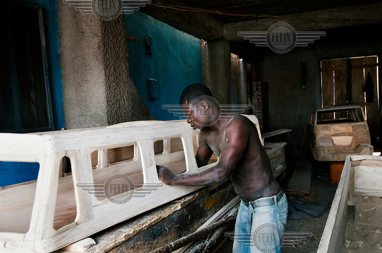 A coffin maker works on a casket shaped like a bus.