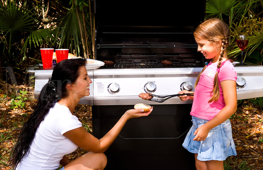 Mother and daughter cooking together outdoors at home with picnic