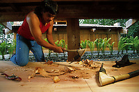 A Native Alaskan Tlingit master carver uses and adz to carve the interior of a canoe. Alaska Native Heritage Cultural Center, Anchorage, Alaska.