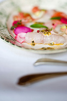 Close up of a dish of sea bass carpaccio served with seafood marinated in a passion fruit and rose water vinagrette and garnished with herbs and rose petals