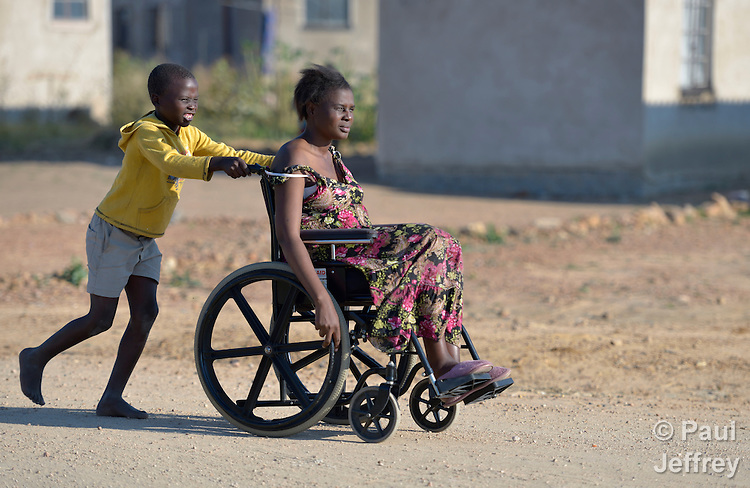 Delina Nleya gets a push from her son Nkosiyazi, 10, on the street near their house in Bulawayo, Zimbabwe. Nleya suffered a spinal cord injury and uses a wheelchair provided by the Jairos Jiri Association with support from CBM-US.