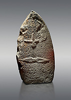 Late European Neolithic prehistoric Menhir standing stone with carvings on its face side. The representation of a stylalised male figure starts at the top with a long nose from which 2 eyebrows arch around the top of the stone. below this is a carving of a falling figure with head at the bottom and 2 curved arms encircling a body above. at the bottom is a carving of a dagger running horizontally across the menhir. the bottom is a carving of a dagger running horizontally across the menhir. Excavated from Piscina 'E Sali VI site,  Laconi.  Menhir Museum, Museo della Statuaria Prehistorica in Sardegna, Museum of Prehoistoric Sardinian Statues, Palazzo Aymerich, Laconi, Sardinia, Italy. Grey background.