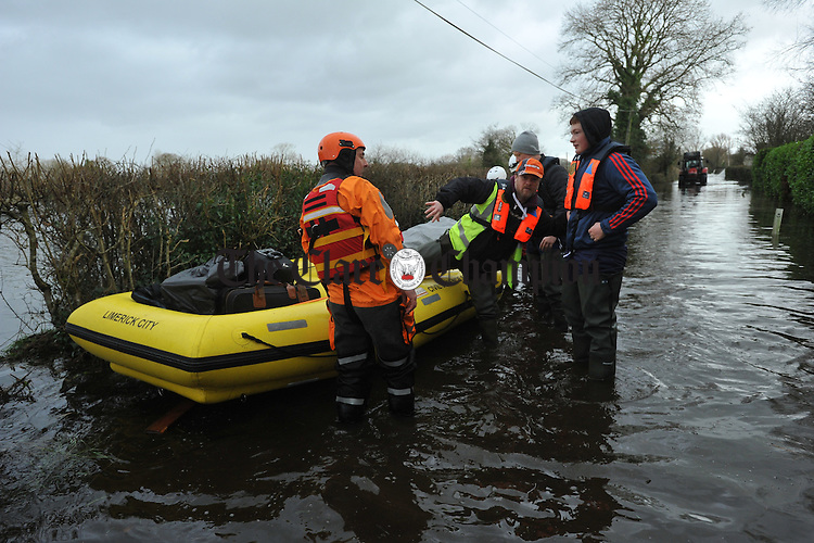 Emergency services evacuate Mike Hogan and his sons Mark and Sean Hogan by boat from their home at Springfield Clonlara where they were cut of by the flood waters. Photograph by John Kelly.