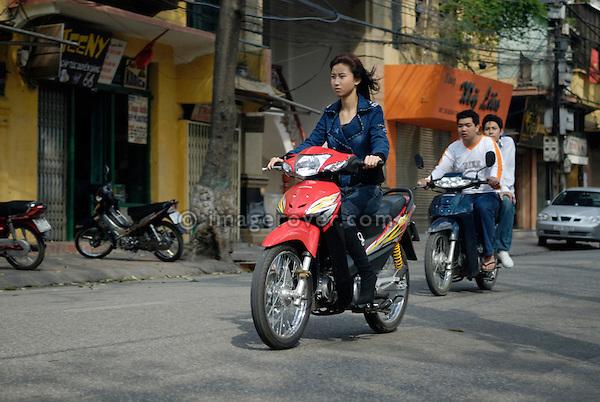 Asia, Vietnam, Hanoi. Hanoi old quarter. Young vietnamese woman riding a small motorbike through Hanoi.
