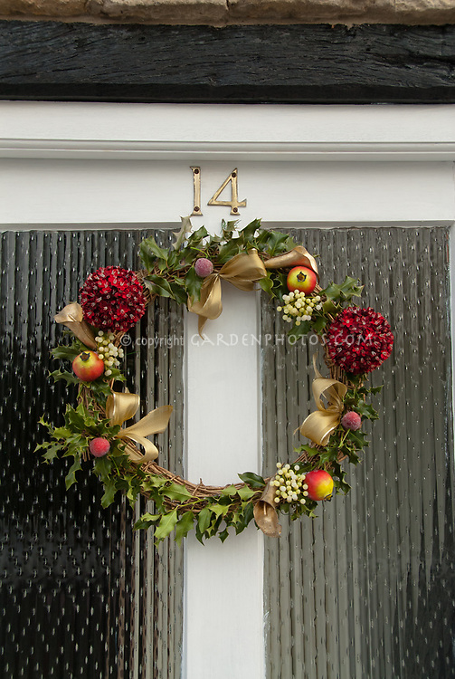Winter holiday wreath on door for Christmas trim decorating. mistletoe, holly, Ilex, ribbons, front door