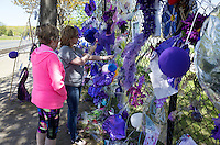 Women photographing Prince's memorial wall of Purple balloons, flowers & notes. Paisley Park Studios Chanhassen Minnesota MN USA