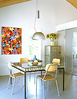 Simple plywood and metal chairs surround the table in the bright and airy dining room which is decorated with a vivid floral painting