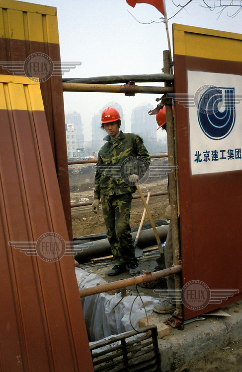 Migrant construction labourer from Henan Province on commercial development site, on what was once hutong housing in Chaoyang, the area now designated as the city's Central Business District (CBD).