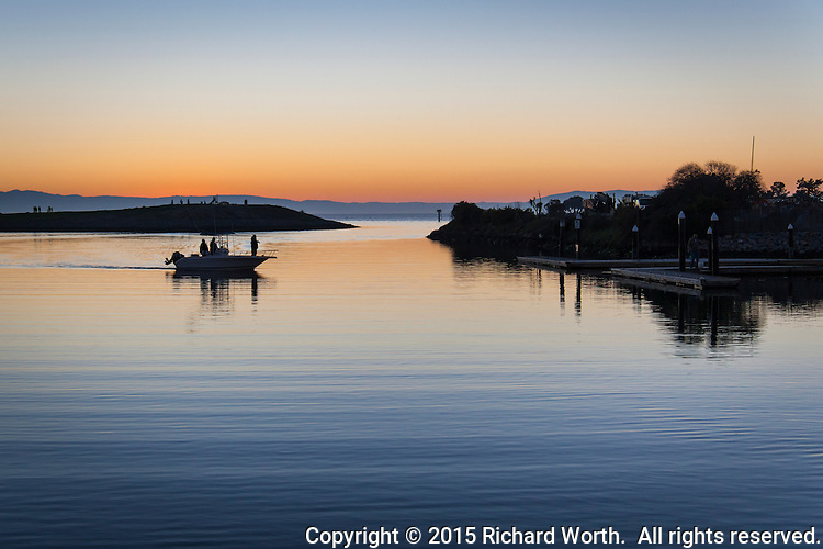 At sunset, a motor boat ends a day of fishing on San Francisco Bay and makes its way to the boat launch ramp at San Leandro's Marina.