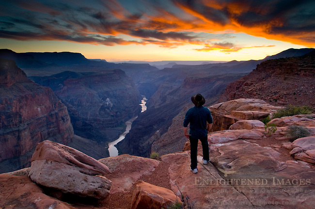 Person standing at the edge of steep rugged cliffs above the Colorado River at sunset, Toroweap, Grand Canyon National Park, Arizona