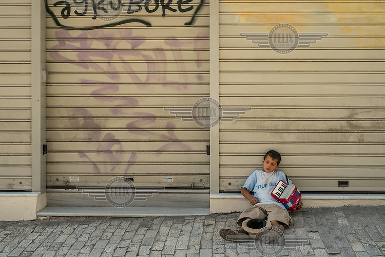 ATHENS, GREECE: a boy who plays music for money in the streets has fallen asleep in a central street of Athens.