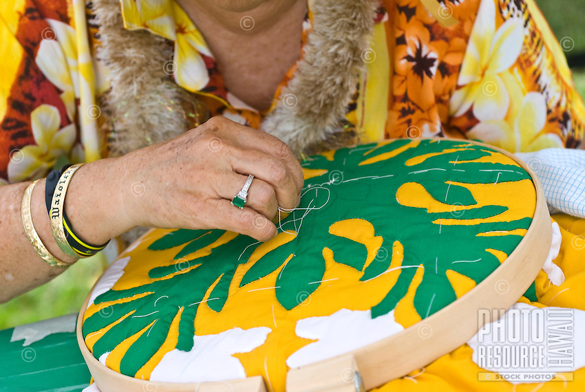 A woman sewing a Hawaiian quilt.