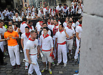 Participants wait the beginning of the third running of the bulls during the San Fermin Festival, on July 9, 2013, in Pamplona, Basque Country. On each day of the eight San Fermin festival days six bulls are released at 8:00 a.m. (0600 GMT) to run from their corral through the narrow, cobbled streets of the old navarre town over an 850-meter (yard) course. Ahead of them are the runners, who try to stay close to the bulls without falling over or being gored. (Ander Gillenea / Bostok Photo)