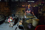 Audelina Vasquez Lopez, a Maya Mam woman, grinds corn for making tortillas and tamales in her home in Tuixcajchis, a small village in Comitancillo, Guatemala. Her 3-year old daughter Nyda looks on.