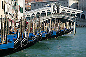 Gondolas on the Canal Grande in Venice with Rialto Bridge in the background.