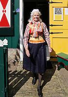 Koningsdag in Marken. Tijdens Koningsdag dragen veel inwoners van Marken klederdracht met oranje accenten. Vrouw verlaat het Marker Museum