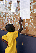 La Lope, Gabon. Boy reading a train timetable with yellow tshirt.