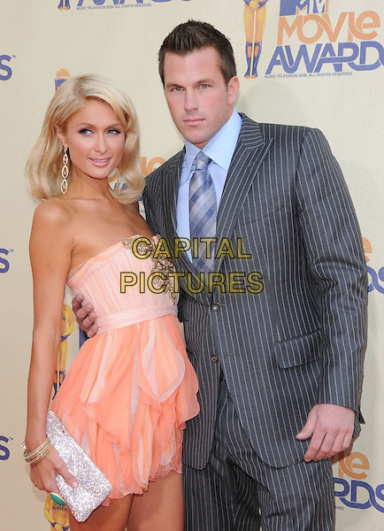 PARIS HILTON & DOUG REINHARDT.The 2009 MTV Movie Awards held at Universal Ampitheatre  in Universal City, California, USA..May 31st, 2009 .half length grey gray pink orange coral strapless dress pinstripe suit couple clutch bag silver jewel encrusted gold bracelet green ring .CAP/DVS.©Debbie VanStory/Capital Pictures.