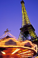 France, Paris, The Eiffel Tower illuminated at night with a carousel spinning