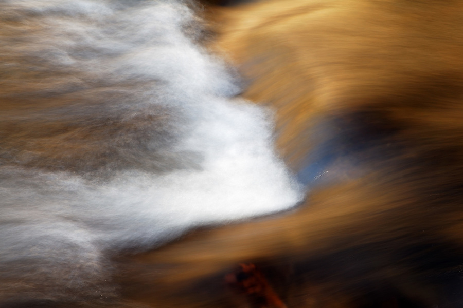 Warm light reflects off of water flowing over rocks, Little Stony Creek, Pembroke, Giles County, Virginia, USA.