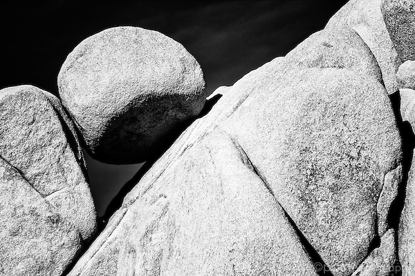 Black and white of round boulder caught in a rock formation.  Taken in infrared