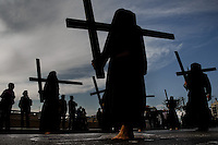 The Holy Week participants (Nazarenos) demonstrate their penance by carrying rough wooden crosses in the processions during the Easter celebration in Malaga, Spain, 7 April 2007.