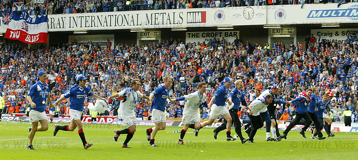 Rangers players link arms and dive bomb onto the gras infront of the Copland Road stand as they win the SPL