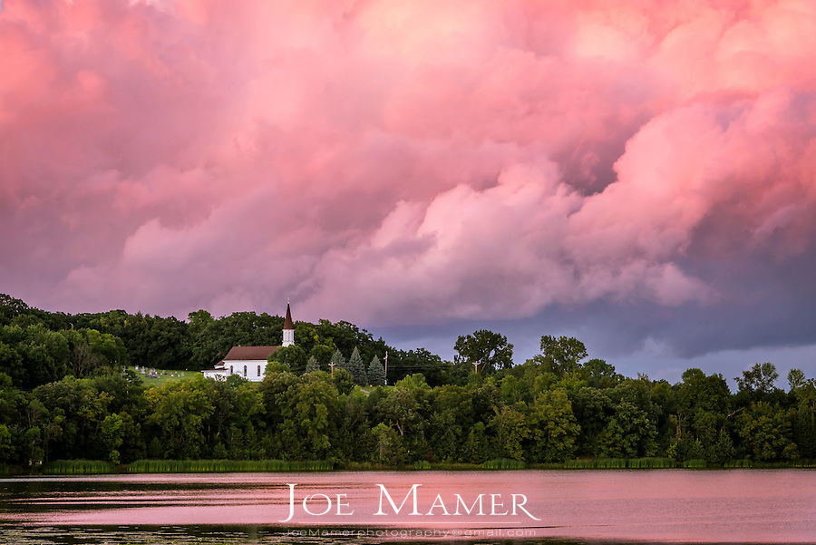 St. Catherine church of Spring Lake, MN with receding storm clouds at sunset.