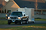 Black Ford F-250 Super Duty towing enclosed trailer.
