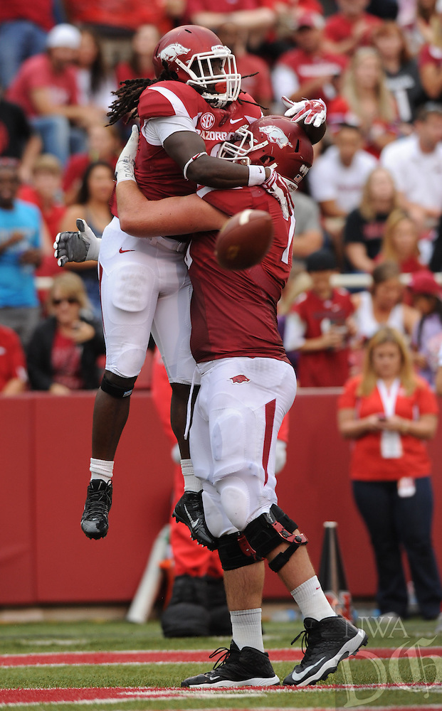 NWA Media/ANDY SHUPE - Arkansas running back Alex Collins, top, celebrates a touchdown with tackle Dan Skipper against Nicholls during the second quarter Saturday, Sept. 6, 2014, at Razorback Stadium in Fayetteville