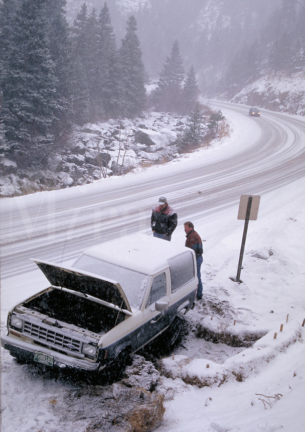 Two Colorado commuters are stuck in a ditch on a snowy canyon road, breaking down, car trouble, automobile, winter scene. Boulder CO USA Boulder Canyon.