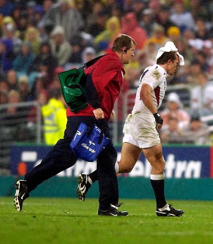 Photo. Richard Lane. .France v England. Semi-final at the Telstra Stadium, Sydney. RWC 2003..16/11/2003..Matt Dawson leaves the field with a blood injury with Doctor Simon Kemp.
