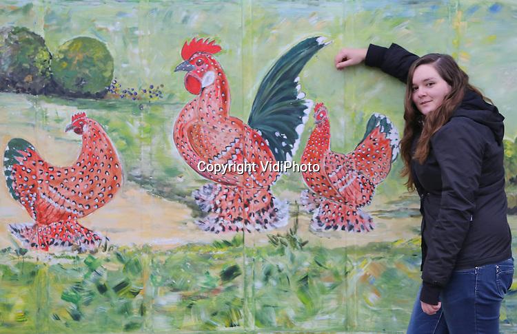 Foto: VidiPhoto<br /> <br /> BARNEVELD &ndash; De twintigjarige Celine van Aalst uit Gouda poseert dinsdag met dubbel gevoel bij het Pluimveemuseum in Barneveld. Omdat ze afgelopen weekend met pluimvee in aanraking is geweest, mag ze tot en met woensdag niet op school komen en daardoor geen examen doen. Het Groenhorst College in Barneveld, voor agrarisch en veterinair onderwijs, hanteert op dit moment strenge hygi&euml;nische maatregelen. Leerlingen uit het gebied rond Gouda waar de vogelgriep H5N8 is uitgebroken, zijn maandag op de school extra gescreend. Van de 50 leerlingen bleken er drie in aanraking te zijn geweest met pluimvee, onder wie Celine. Zij moet nu het examen op een ander tijdstip maken. Ook de gezondheid van de betreffende studenten is onderzocht, omdat de variant van de vogelgriep die is aangetroffen, ook gevaarlijk is voor mensen. Volgens directeur W. G. de Haas van het Groenhorst College mag juist van een agrarische onderwijsinstelling worden verwacht dat de richtlijnen van de overheid inzake de vogelgriep streng worden gehandhaafd.  &ldquo;De meeste leerlingen van ons werken met levende have, hier en op de stagebedrijven. We nemen daarom geen enkele risico, ook al omdat we op school zo&rsquo;n 100 soorten dieren verzorgen. Zo hebben we ook ontsmettingsmatten neergelegd bij de ingang. Het hanteren van hygi&euml;nische richtlijnen vormen een deel van de opleiding en we geven daarmee het goede voorbeeld. Leerlingen en hun ouders zijn daar zeer over te spreken&rdquo;, aldus De Haas.