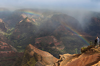 A woman and a man enjoy the overview of Wamea Canyon with a rainbow, Kaua'i.