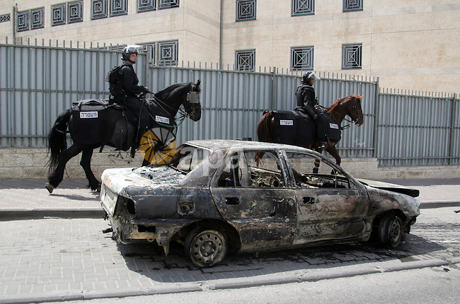 An Israeli border policeman rides past a car which was torched during riots in the East Jerusalem neighborhood of A-Tur, on 13 May 2011, as riots broke out in several flashpoints in East Jerusalem following the Friday Prayers. Israel bolstered its security in Jerusalem ahead of the Palestinians marking 'Nakba Day,' the Palestinian term for the 'catastrophe' when Palestinians were uprooted from their homes and land and made refugees, with the establishment of the State of Israel.  Photo by Mahfouz Abu Turk