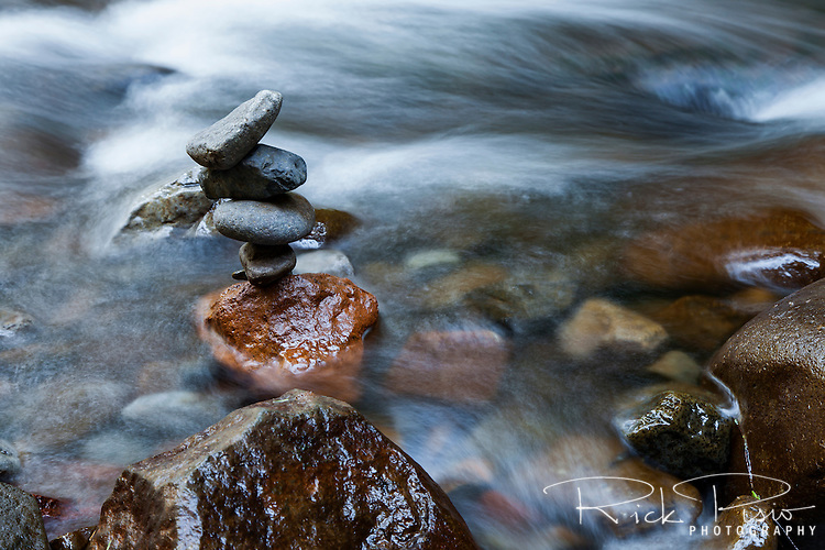 Rushing waters surround a rock cairn in Multnomah Creek above Multnomah Falls along the Columbia River in Northern Oregon.