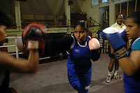 INDIA (West Bengal - Calcutta)July 2007, Shakila Babe  and Shanno Babe during  practice at Sports Authority of India Complex (East Zone) in Kolkata. Shakila and Shanno are twins from a poor muslim family of Iqbalpur, Kolkata. . Inspite of their late father's unwillingness to send his daughters to take up  boxing her mother Banno Begum inspired them to take up boxing at the age of 3. Their father was more concerned about the social stigma they have in their community regarding women coming into sports or doing anything which may show disrespect to the religious emotions of his community. Shakila now has been recognised as one of the best young woman boxers of the country after she won the  international championship at Turkey in the junior category. Shanno is also been called for the National camp this year. Presently Shakila and shanno has become the role model in the Iqbalpur area  and parents from muslim community of Iqbalpur have started showing interst in boxing. Iqbalpur is a poor muslim dominated area mostly covered with shanty town with all odds which comes along with poverty and lack of education. - Arindam Mukherjee