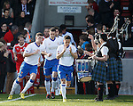 The teams runout past a pipe and drum guard of honour