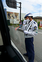 A checkpoint at the edge of the town of Namie, Fukushima Prefecture, Japan, August 2, 2013. The town of Namie was evacuated following the nuclear accident of March 2011. Residents can only return for short periods to tend to their former homes and pick up belongings, and are not permitted to stay overnight.