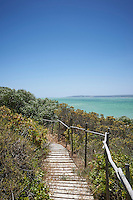 A wooden decked coastal path with rustic handrail