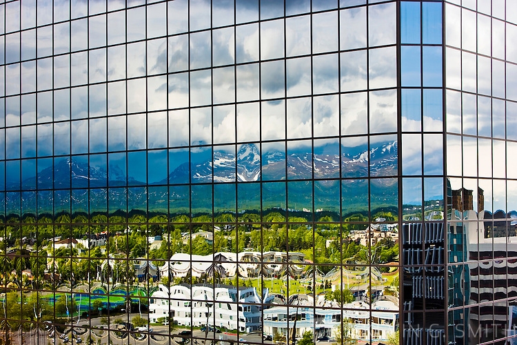Midtown Anchorage land the Chugach Mountains reflected in windows of the Atwood Tower, summer, Anchorage, Southcentral Alaska, USA.