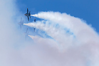 The Blue Angels diamond formation performs a rolling maneuver leaving a trail of smoke behind.