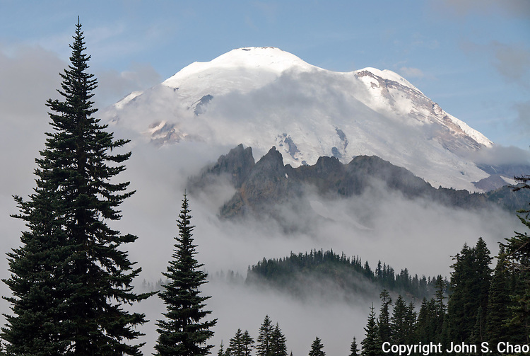 Volcanic Mount Rainier's 14,410-foot high summit peeks above layers of morning mist and clouds rising between rugged mountain ridges and evergreen valleys. Taken near Tipsoo Lake, Mount Rainier National Park, Washington State.....Photographed on digital media.