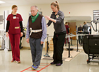 NWA Democrat-Gazette/DAVID GOTTSCHALK Edward VanDuzer (center) is assisted by Heather Vaughn (left), physical therapist, and Sharina Cassity, student of Physical Therapy, Tuesday, February 13, 2018, during a balance and mobility exercise at the University of Arkansas for Medical Sciences Northwest Outpatient Therapy Clinic in Fayetteville. The physical therapy program is new and the first cohort of 24 students is expected to graduate this May.