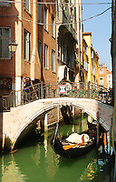 Gondola under bridge in venetian canal